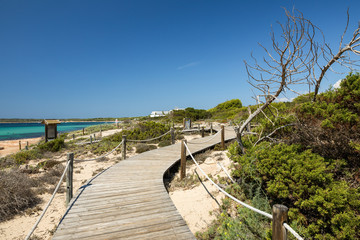Wooden walking path on the Migjorn beach, Formentera island. Spain.