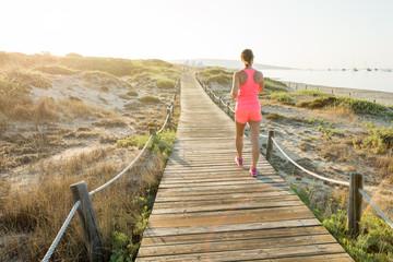Woman walking, running on the wooden path along sandy beach. Migjorn beach, Formentera island. Spain.