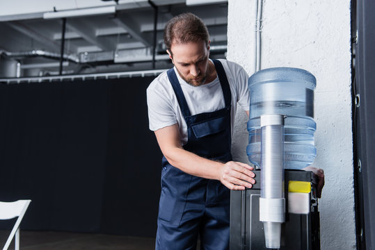 serious handyman in working overall checking broken water cooler