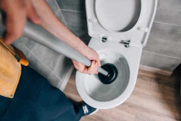 cropped shot of male plumber using plunger and cleaning toilet in bathroom