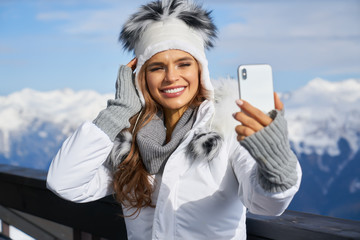 Woman skier making selfie photo on the background of snowy high mountains and