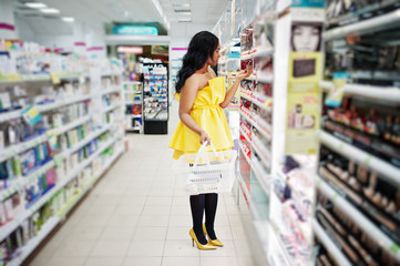 Stylish african american woman at yellow dreess posed at cosmetic store, buying with basket make up accessories on beauty shop.