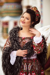 Beautiful happy woman is wearing traditional russian clothes in winter park