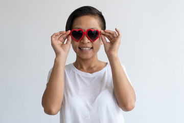 Smiling Asian woman adjusting heart shaped sun glasses. Lady wearing t-shirt and looking at camera. Valentines Day concept. Isolated front view on white background.