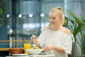 Young blonde girl is eating mixed vegetable salad in cafe. Portrait of a young attractive woman eating salad at cafe table. The concept of healthy eating. Toning