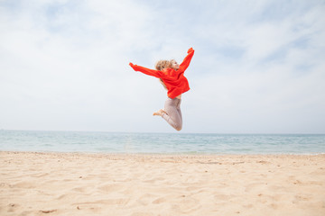 woman jumps into top and sandy sea Beach