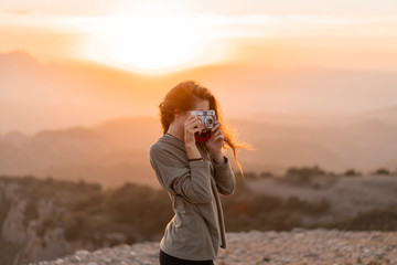 Woman taking picture with vintage camera during sunset