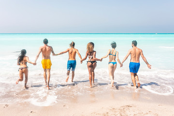 Group of friends at the beach, running into the sea, holding hands