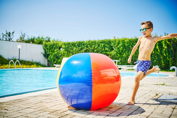Shirtless boy playing with beach ball at poolside