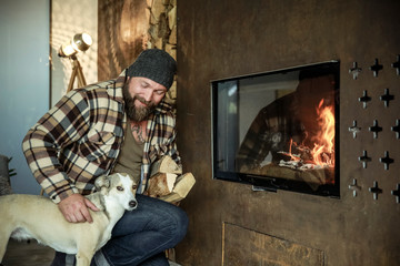 Bearded man with his dog in front of fireplace at home