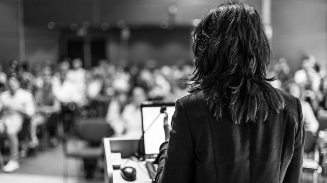 Female speaker giving a talk on corporate business conference. Unrecognizable people in audience at conference hall. Business and Entrepreneurship event. Black and white image.