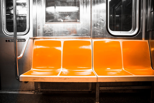 View inside New York City subway train car with vintage orange color seats