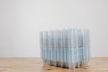 Perspective view of a pile of empty plastic egg boxes on a table