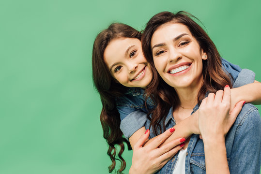 portrait of cheerful mother and daughter embracing and looking at camera isolated on green