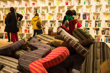 Kissenchaos in Leselandschaft vor Bücherwand
