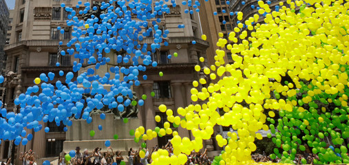 People take pictures of balloons being released in the sky of downtown Sao Paulo as part of year-end celebrations