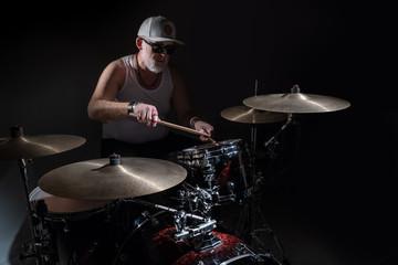 The old drummer on a dark background