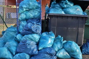 Blue garbage bags against dark grey dustbins for waste separation. Recycling in germany.