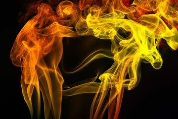 Colorful smoke of incence stick isolated at black background