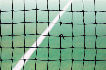 A hole in a tennis net on court