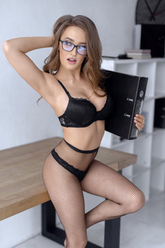 Sexy girl secretary in black lingerie and glasses poses in a bright office