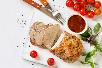 Baked Meat. Roast pork Meat with honey-mustard glaze served on a chopping board with ketchup on kitchen table. Top view flat lay background. Copy space.