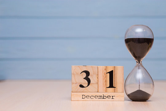 December 31st set on wooden calendar and hourglass with blue background.