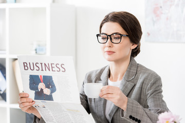 attractive businesswoman reading newspaper and holding cup of coffee in office