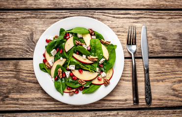 spinach salad, apple, pomegranate, cheese, walnut salad on wooden steel