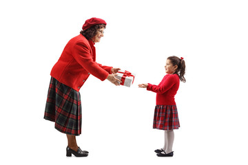Senior lady giving a present to a little girl