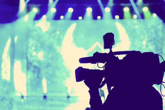 Professional Video camera operator working with his equipment, blue background