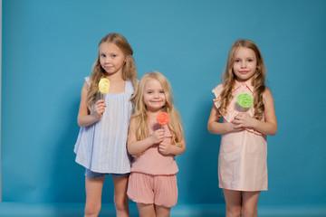 three little girls girlfriend eaten sweet candy lollipop on a stick