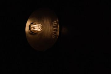 Detail of an Edison lightbulb with dark background