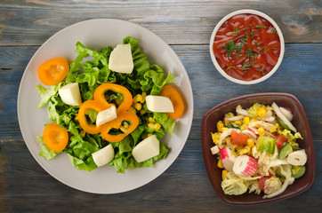salad of cheese, lettuce, corn, pepper on a wooden background. Vegetarian salad on a plate.