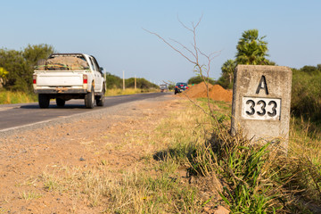 A pickup truck hurrying by A333 milestone (kilometre mark) along the highway number 9 Ruta Transchaco, Gran Chaco, Paraguay, Latin America, South America
