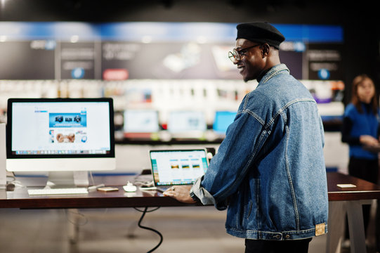 Stylish casual african american man at jeans jacket and black beret using new laptop at electronics store.