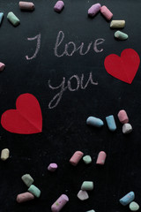I love you, written chalk on a blackboard. Happy Valentines Day. Valentine's Day theme. Mother's Day. Chalk lettering on blackboard with paper red hearts. Colored chalk lying on a black school board