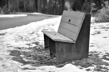 resting bench along hiking path in park in winter