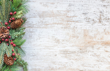 Christmas background with fir tree, red berry and decoration on white wooden board.Top view with copy space.