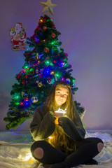 Young girl with christmas tree soft focus low light. Young girl holding sparklers for christmas during winter alone, with beautiful christmass tree bokeh lights in the background