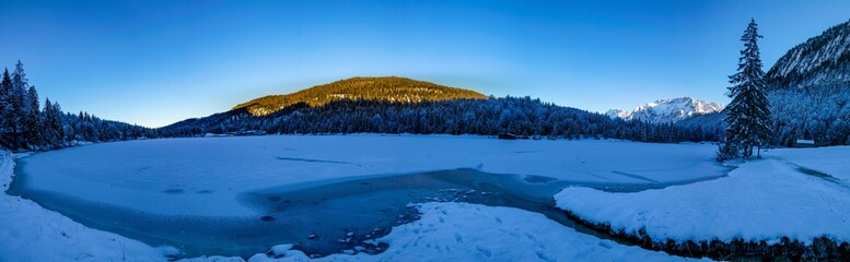 Blick auf den zugefrorenen Ferchensee und den zugeschneiten Alpen in Mittenwald