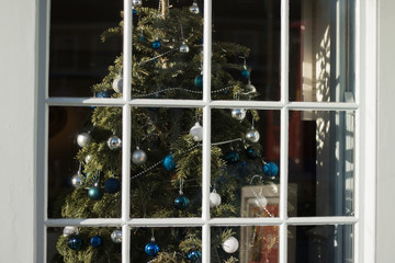 Beautiful festive traditional Christmas tree is inside house. View through window. Concept: happy Christmas & New Year winter holidays.