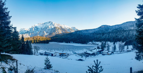 Blick auf den zugefrorenen Lautersee und den zugeschneiten Alpen in Mittenwald