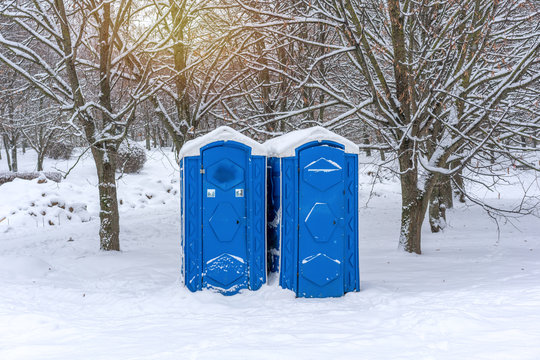 two blue portable plastic toilets in the park in winter