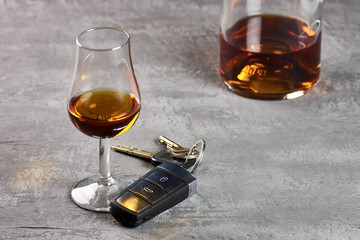 Glass and bottle of whiskey on a stone table top and car keys. Driving in drunkenness.