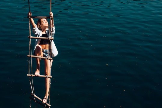 Her ambition is too far. Pretty woman climb jacobs ladder to the top. Sensual woman hang on rope over water surface. Sexy woman climbing up rope ladder. Achieving her towering ambition, copy space