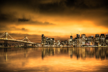 Wall Mural - View of San Francisco skyline under golden sunset sky with lights and Bay Bridge