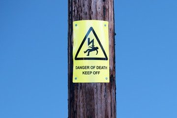 Danger of death safety sign on wooden telegraph post against blue sky