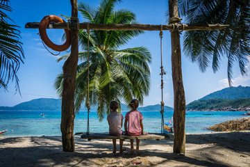 Kids staring at the ocean on a swing at the beach of Perhentian island, a tropical paradise in Malaysia