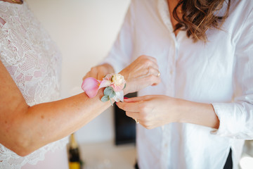 woman putting on wrist corsage for wedding
